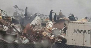 People inspect the wreckage following a jet crash near Grand Bahama International Airport in Freeport, Bahamas.